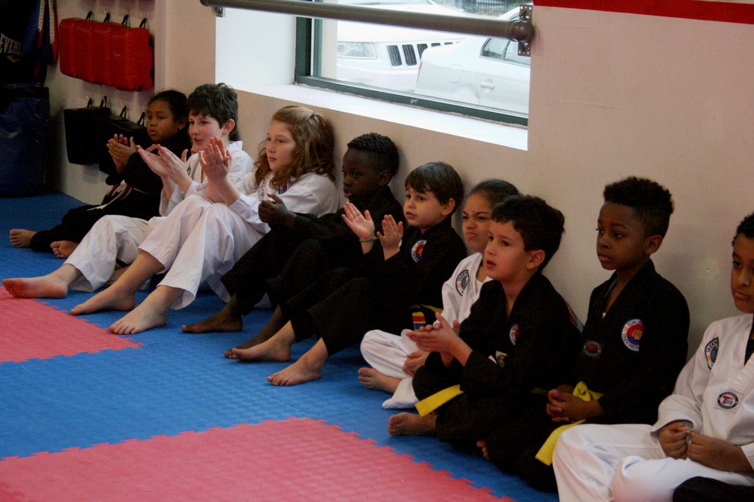 A row of kids in white and black Taekwon-do uniforms sit and watch the test