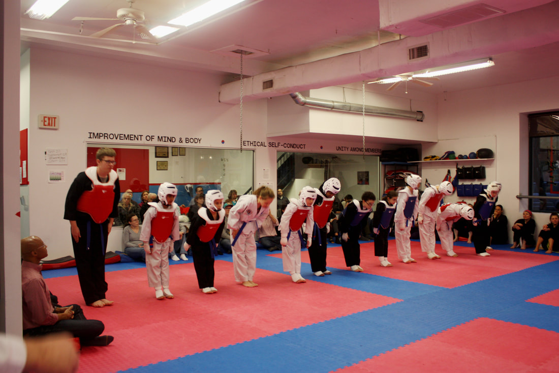 A row of students in sparring gear bow to the judges at the test