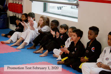 Kids in white and black Taekwon-do uniforms sit along a wall and watch the test